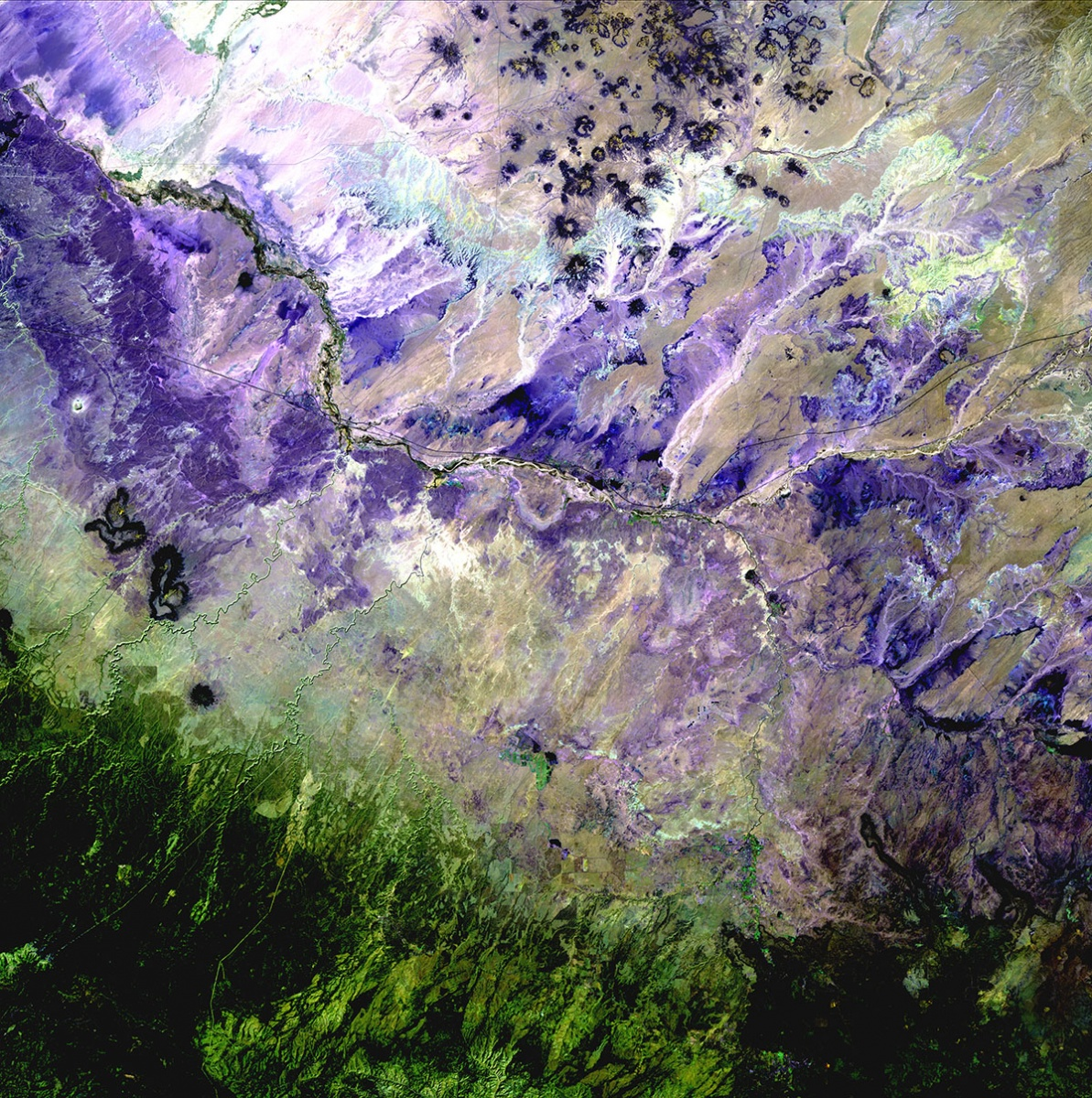 A satellite photo taken of the  a landscape transitioning from blues and purples to greens.