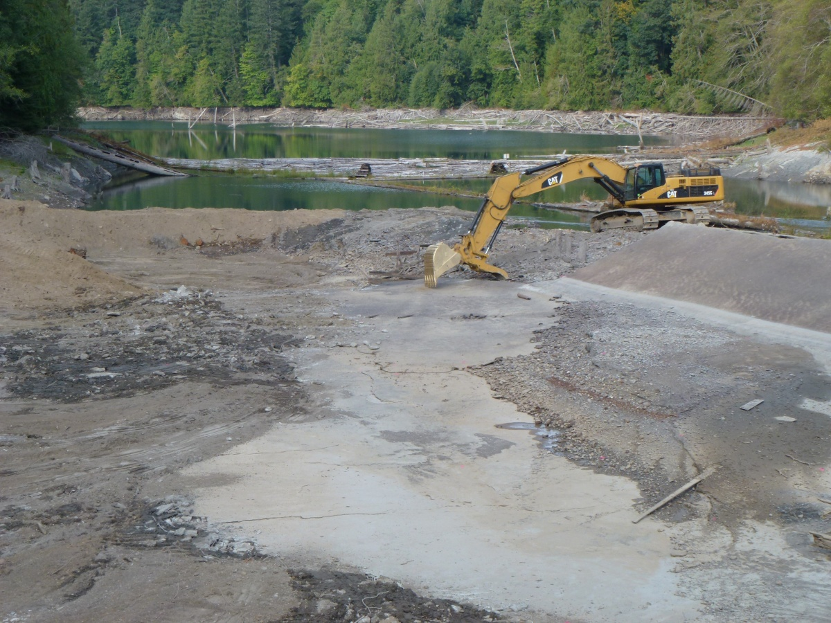 A large piece of heavy machinery moves dirt while removing a dam on a river.