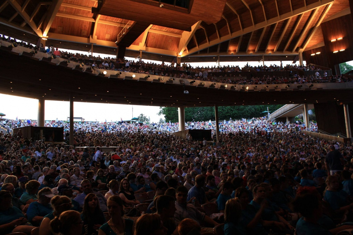 A huge crowd fills a covered amphitheater to watch a concert.