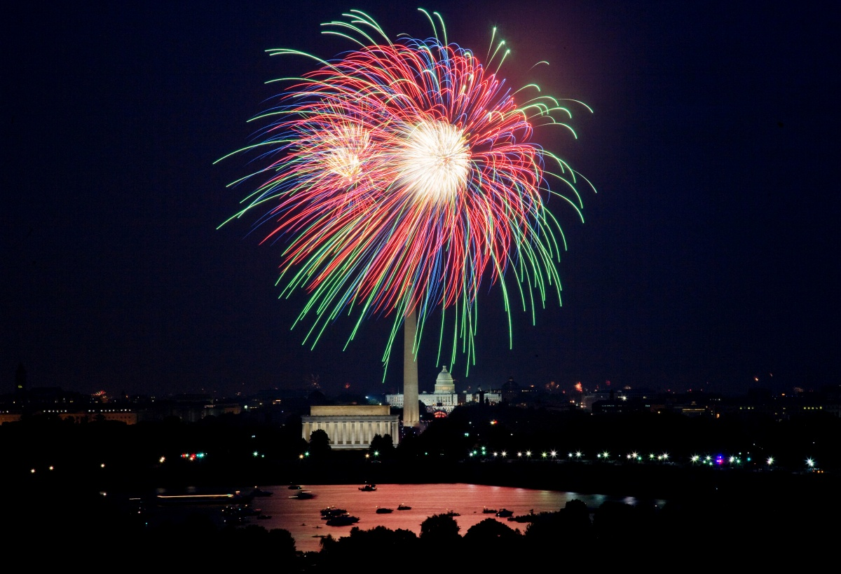 The Lincoln Memorial and Washington Monument are illuminated by a bright, multi-colored firework blast.