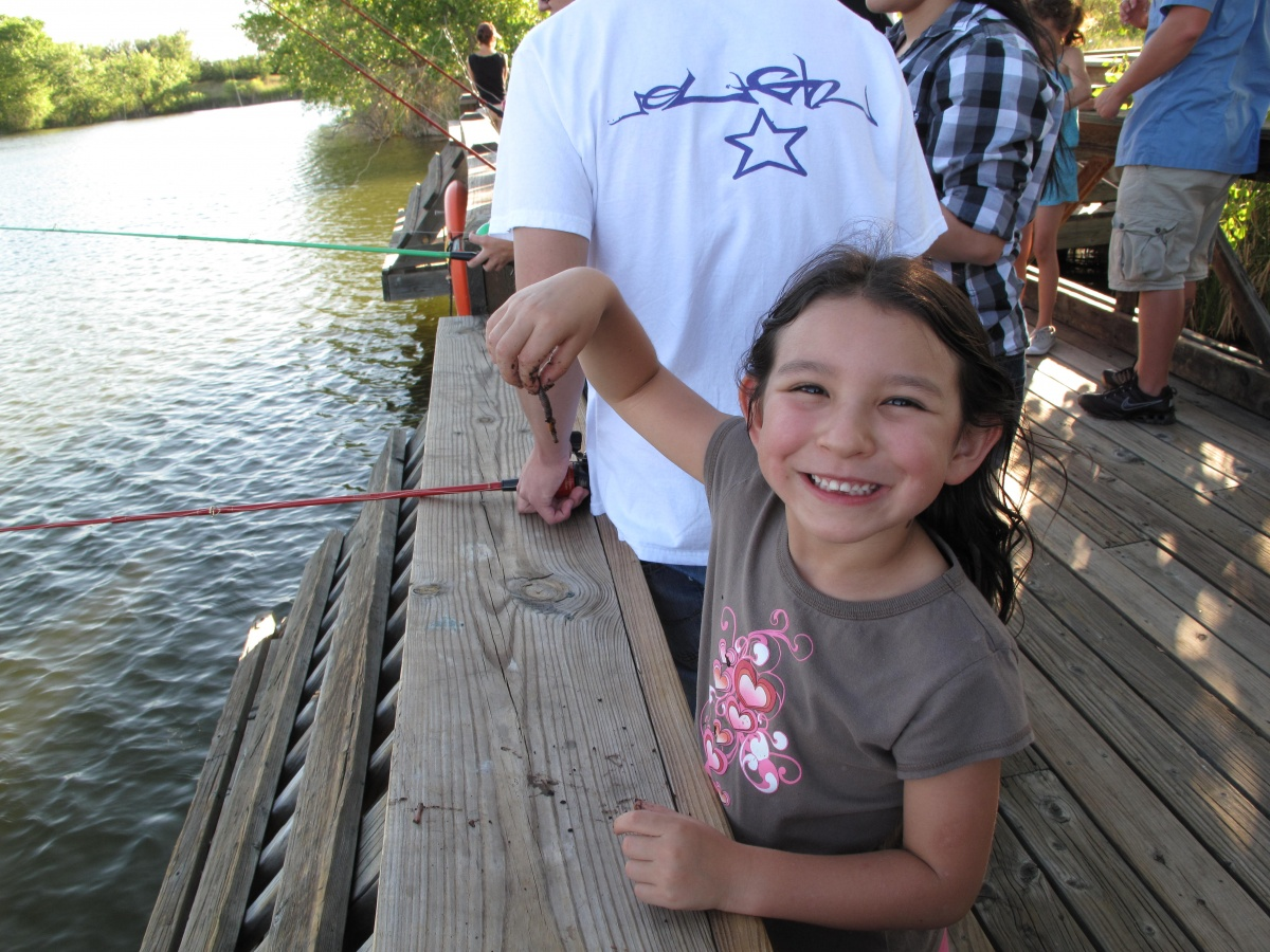 A little girl holds up a worm while standing on a dock with people fishing in a river.