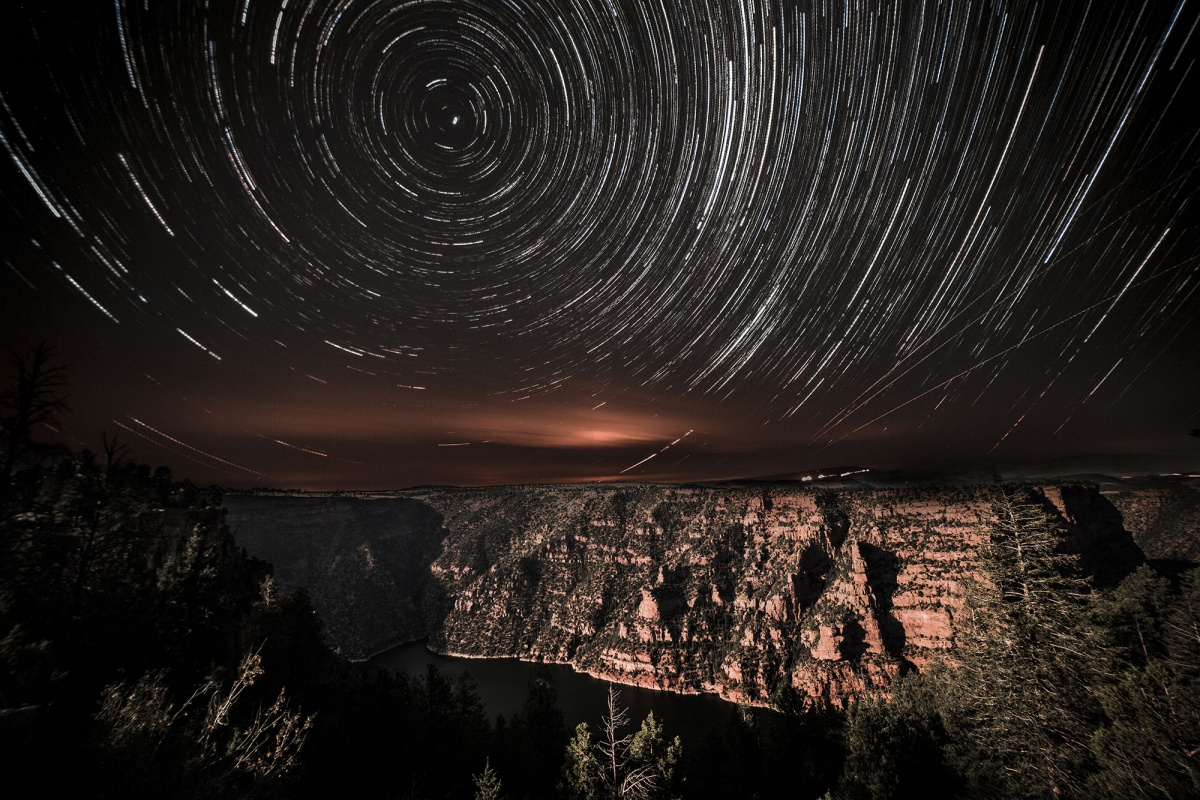 Stars appear to shoot in a perfect circular motion, creating the appearance of rings in the dark sky. The rocks and trees below appear bright from the light.