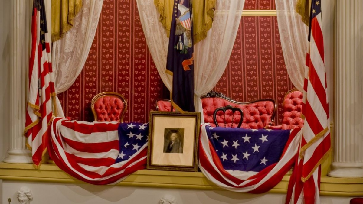 A theater box with red wallpaper and fancy red chairs is draped with american flags and a portrait image sits in front.