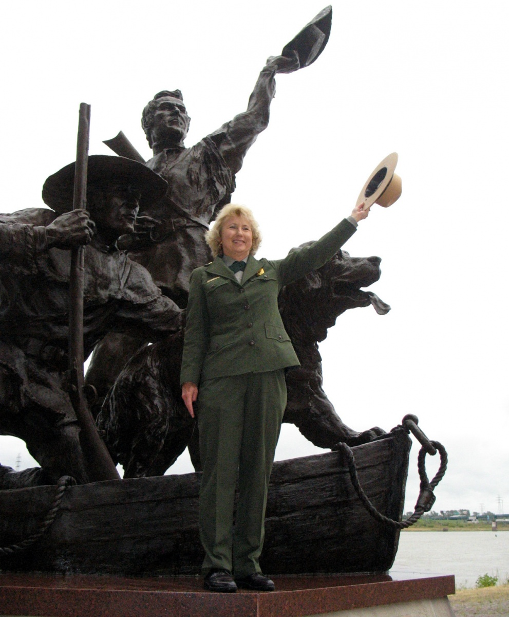 Fran Mainella -  a woman with blond hair wearing a national park service uniform -  stands in front of a statue of two men and a dog holding her hat in the air.