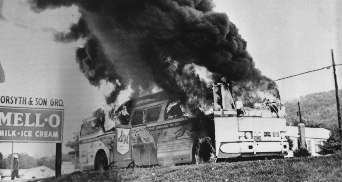 An old photo of a greyhound bus burning by the side of a highway.