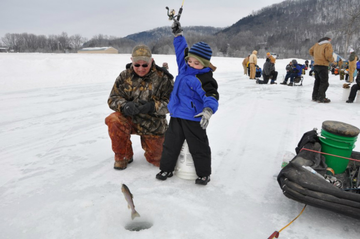 Standing on a frozen lake, a boy uses a fishing rod to pull a fish out of a hole in the ice with an older man helping him.