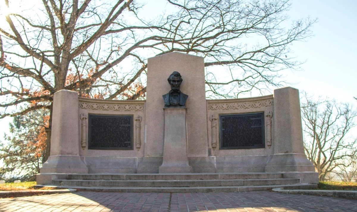 A long white stone memorial with a grey bust of Lincoln's head sits in front of branches with a few orange leaves.
