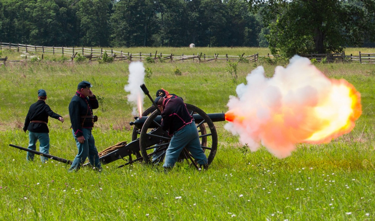 Four volunteers dressed as union soldiers fire a cannon in the middle of the field.
