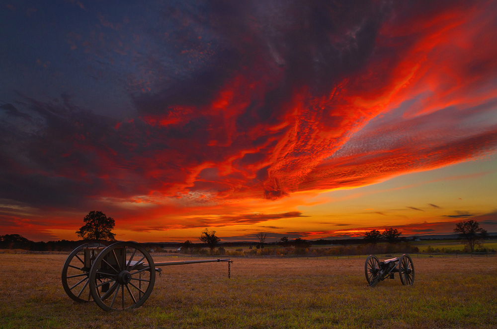 red skies over a grassy meadow with two cannons