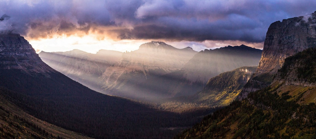 sun rays stream through clouds into a valley