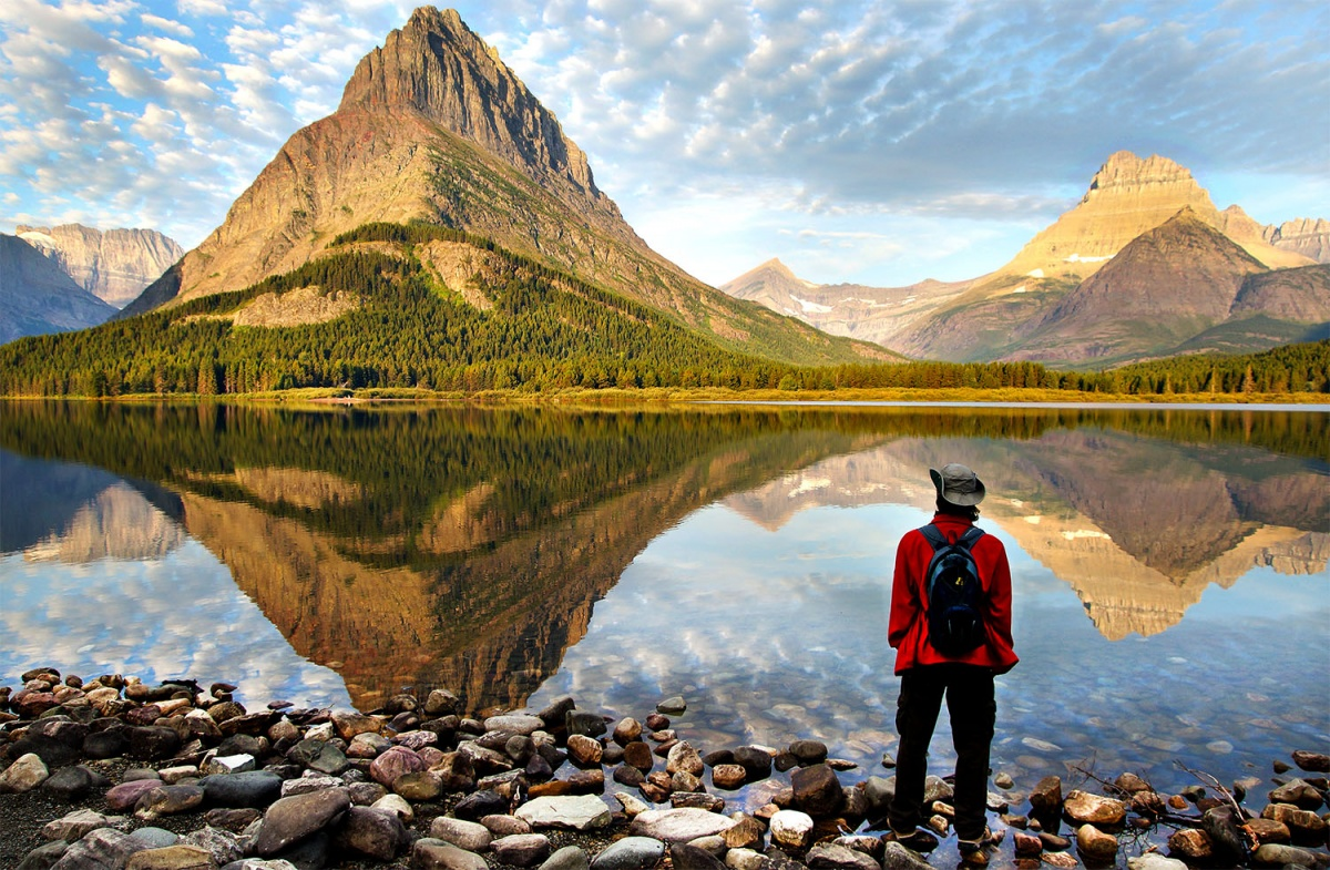 a man marvels at the view of a mountain reflected in a lake