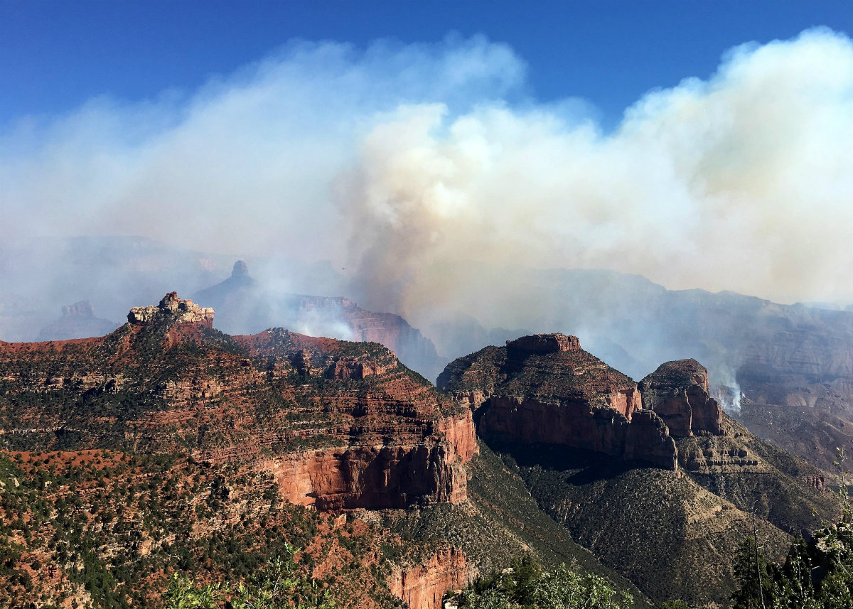 White-yellow smoke billows from behind layers of orange canyon wall covered in brush