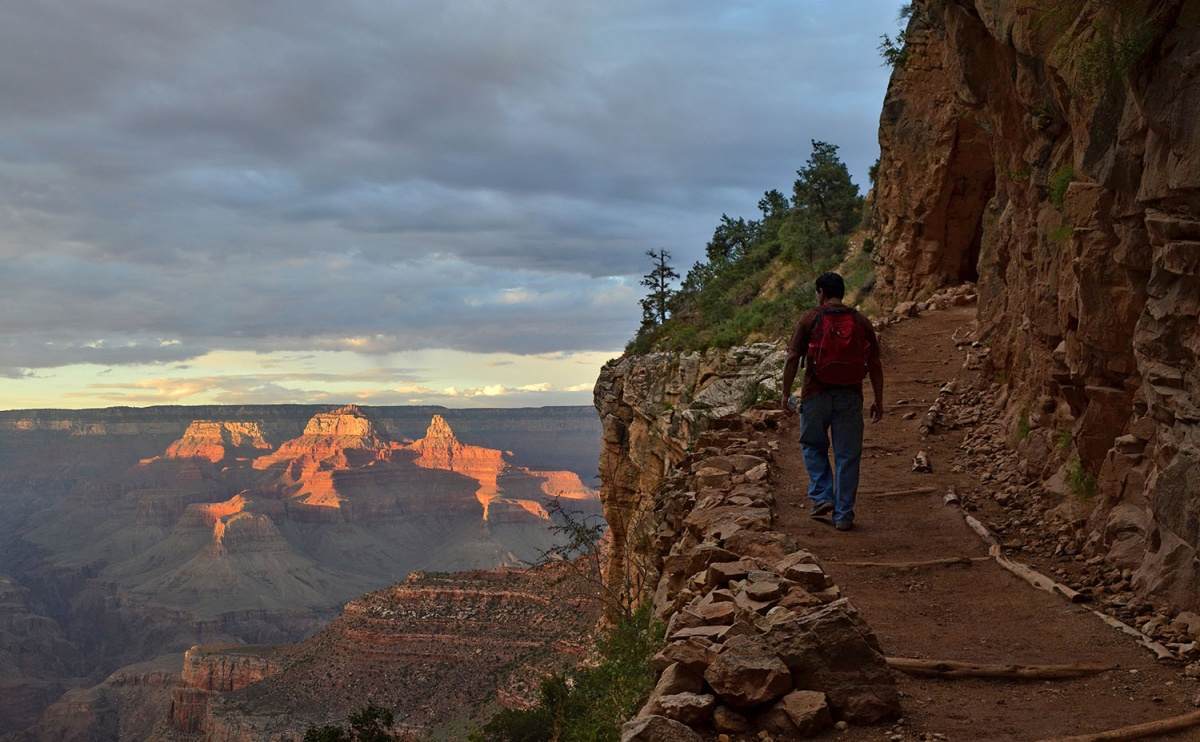 A hiker walks along a trail up the side of the Grand Canyon at sunset