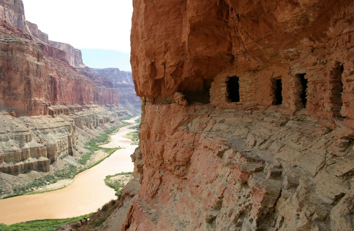 On the right side of the picture is a rough wall of deep red with caves lined up, carved into the Canyon wall. On the left is another wall of a lighter orange shade towering over a muddy Colorado river