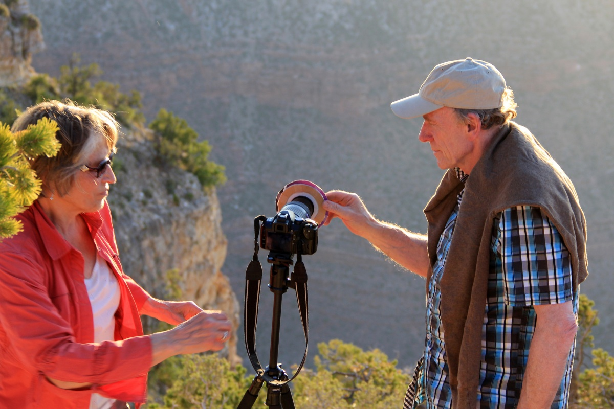 A man and a woman make adjustments to a camera on a tripod while looking out over the cliff wall of a massive canyon.