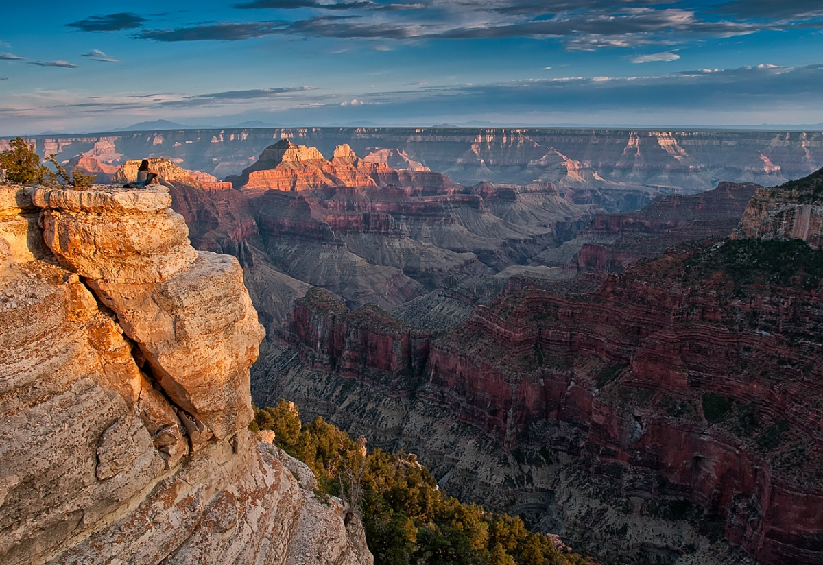 The dark and light layers of the walls of the Grand Canyon shine in fading light.