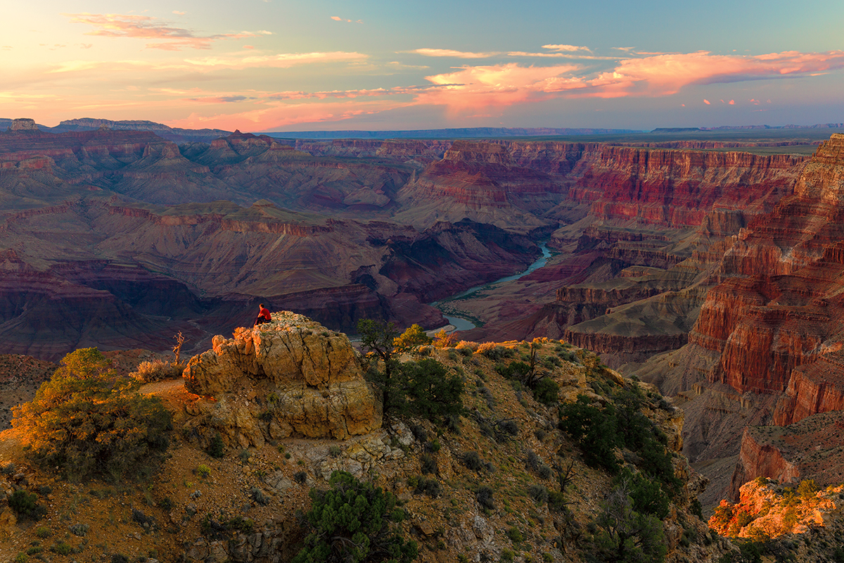 An off-screen sunset paints an elevated rock yellow as a man perched on top, looks into the distance. The canyon is a range of purple and oranges extending into the horizon and anchored by a brilliant blue Colorado river
