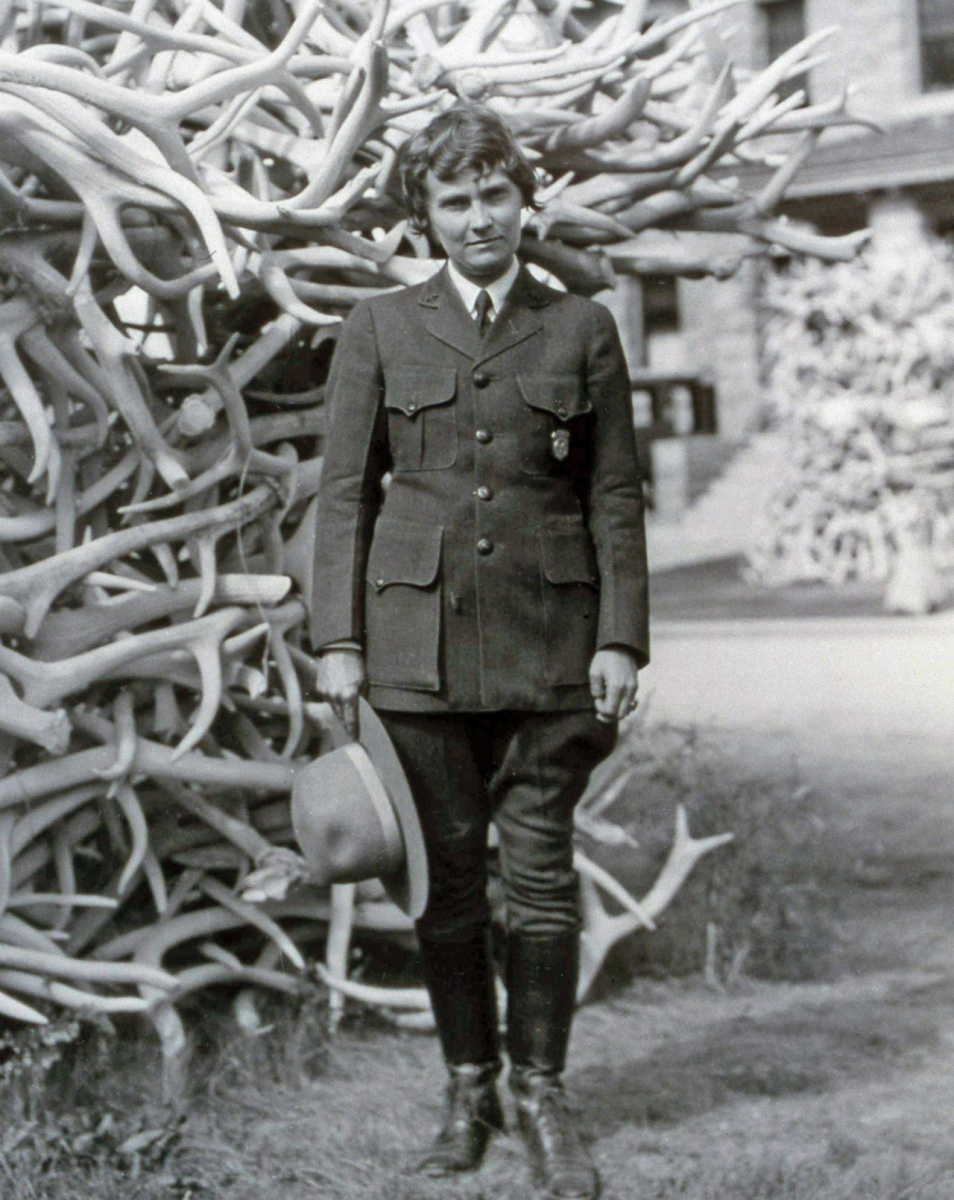 A historic black and white photo of Herma Baggley wearing her National Park Service uniform and standing in front of a tall pile of elk antlers.
