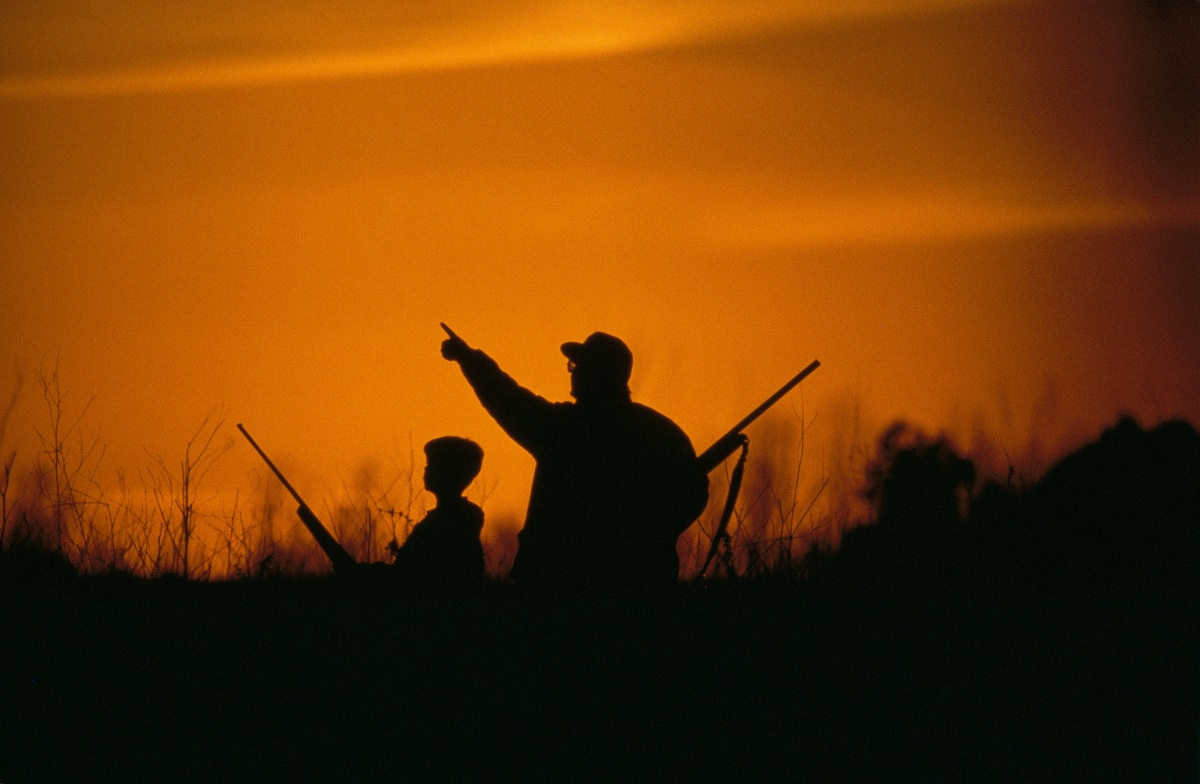 The silhouettes of a young boy and his father hunting as the sky glows orange.