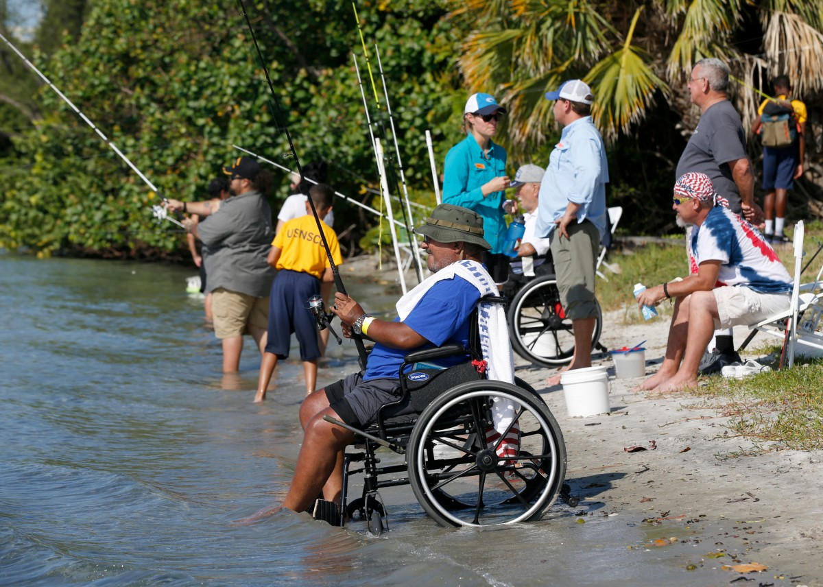 Several veterans relax on the sand at the water's edge, casting their lines into the clear water and socializing among family and friends with green bushes rising in the background.