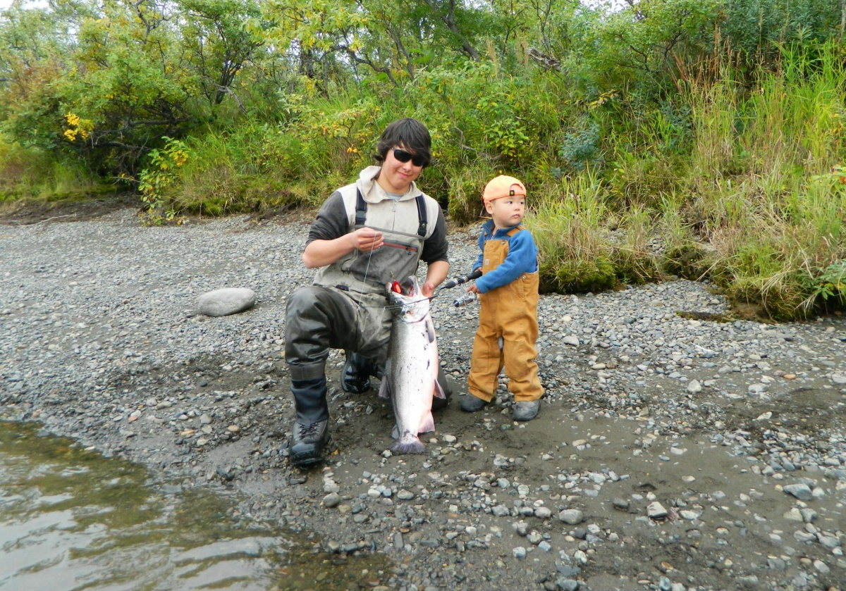 A young man and a boy hold a fish on the bank of a river in Alaska.