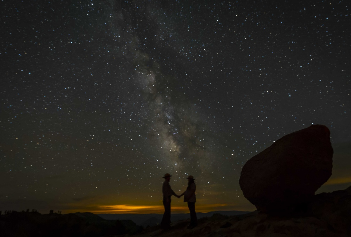 sky full of stars with two people silhouetted