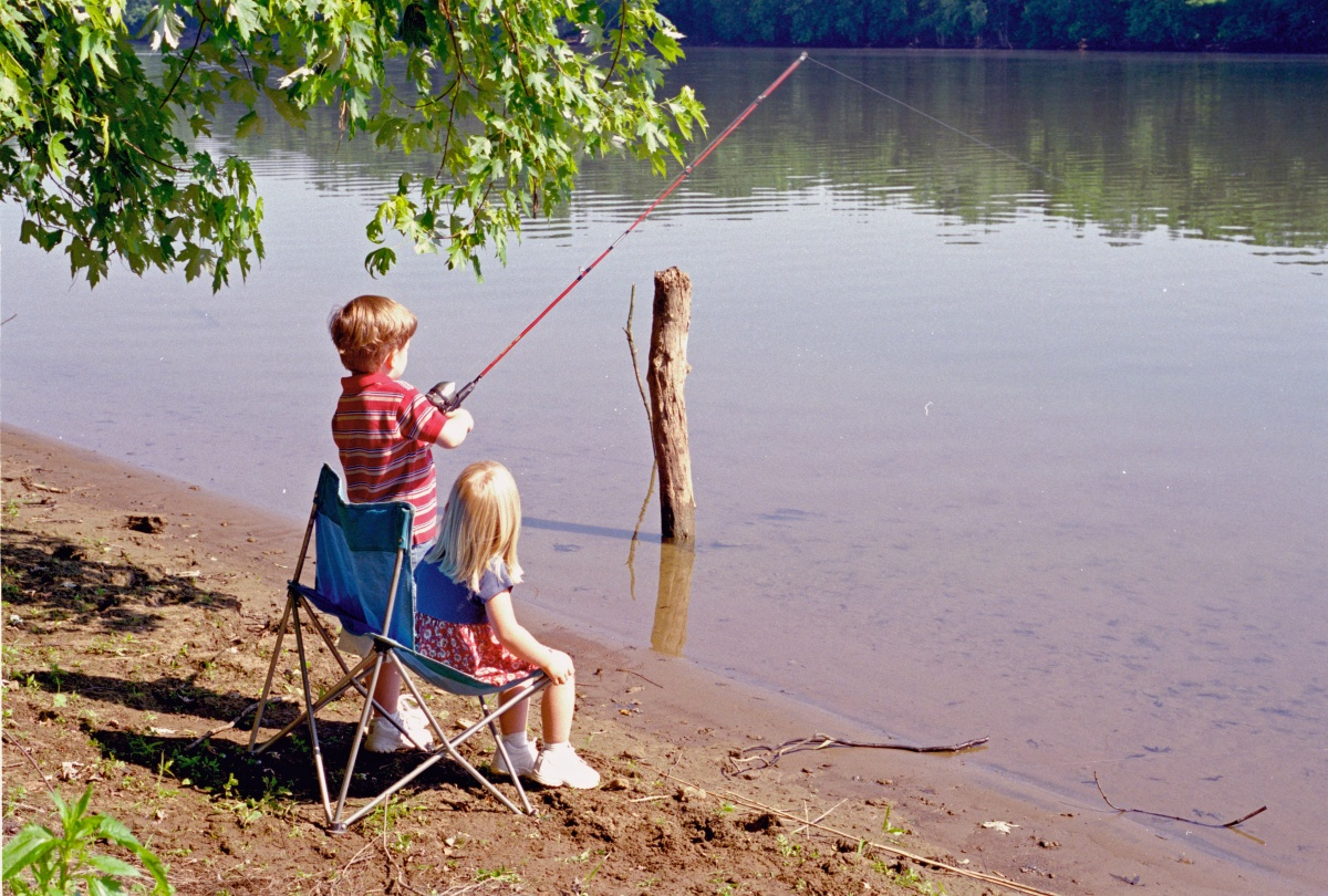 Two young kids cast a pole to fish along the banks of the Ohio River.