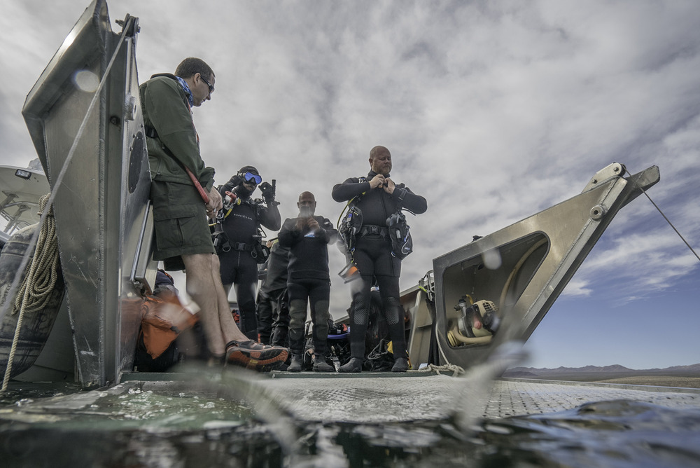 Three veterans stand next to the water on the edge of a boat's gray deck, adjusting their diving gear and goggles with blue skies and clouds high above.