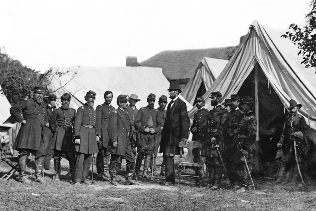 A historic image of President Lincoln in his top hat surrounded by officers in uniform in front of tents.