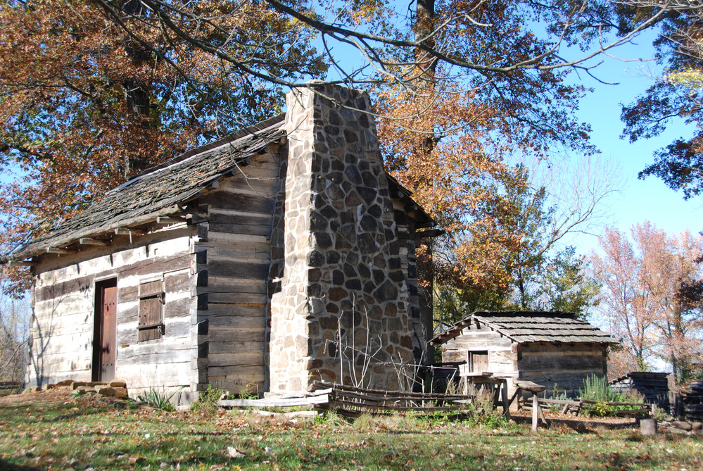 An old log cabin stands in the middle of autumn trees with a blue sky and green grass.