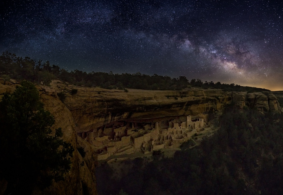 stars over ancient building in the cliffs