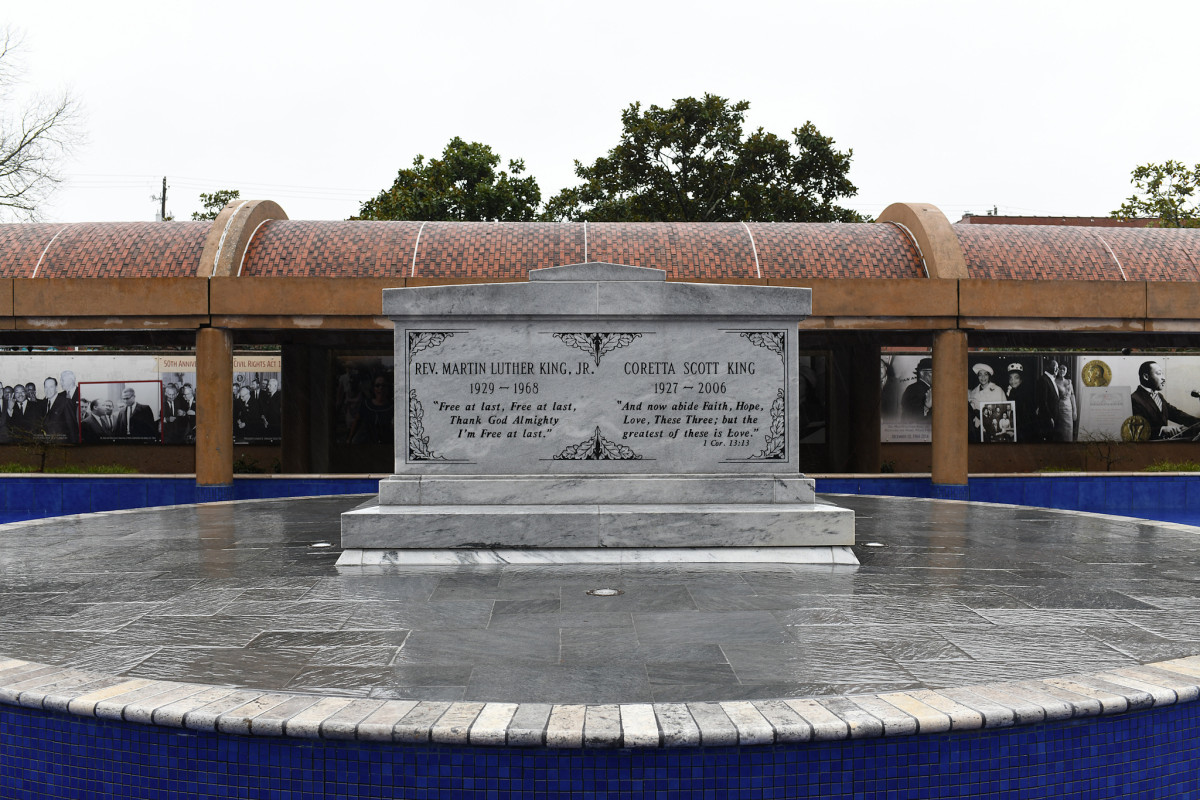 The large gray stone tomb of Dr. and Mrs King stands on a circular platform surrounded by a shallow pool of water.