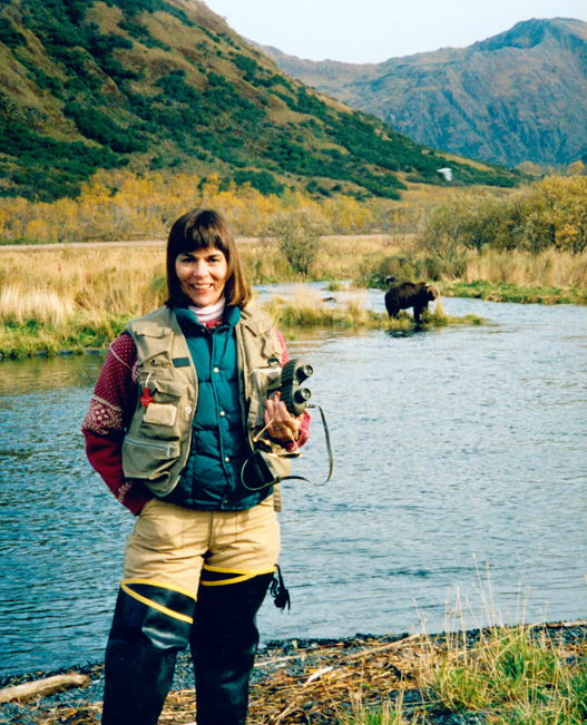 Mollie Beatie - a woman with brown hair wearing fishing gear - stands on a riverbank holding binoculars as a bear stands in the background.
