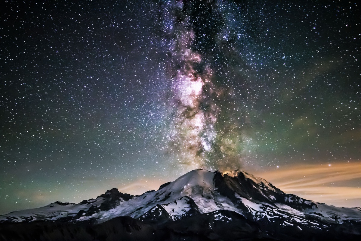 The milky way appears to erupt from a snow covered mountain.