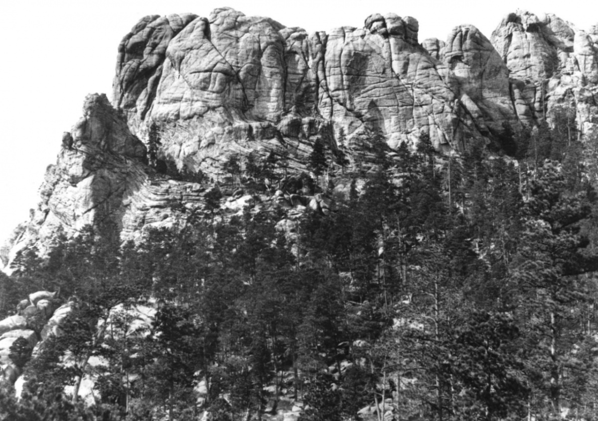 Photo of Mount Rushmore before the faces were carved in it. A tall rocky cliff with trees at the base.