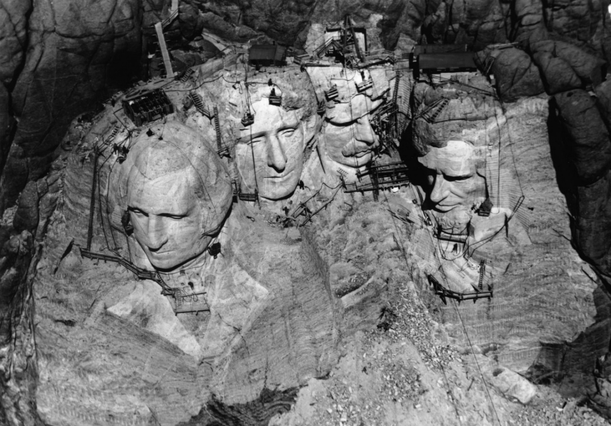 A historic aerial photo of Mount Rushmore under construction. The four heads of the memorial are covered in cranes and workers.
