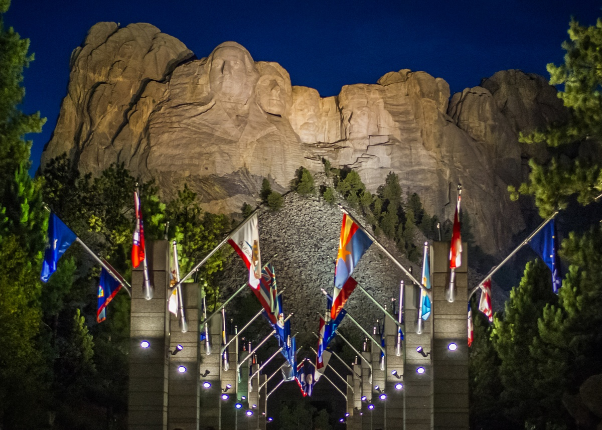 An outdoor walkway lined with state flags moves towards the sculpture on Mount Rushmore.
