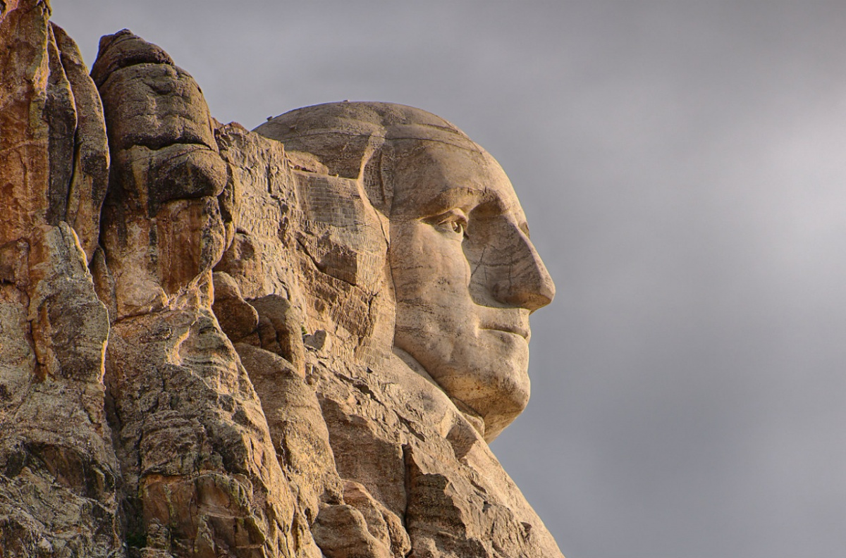 The face of George Washington is carved in stone on the side of Mount Rushmore.