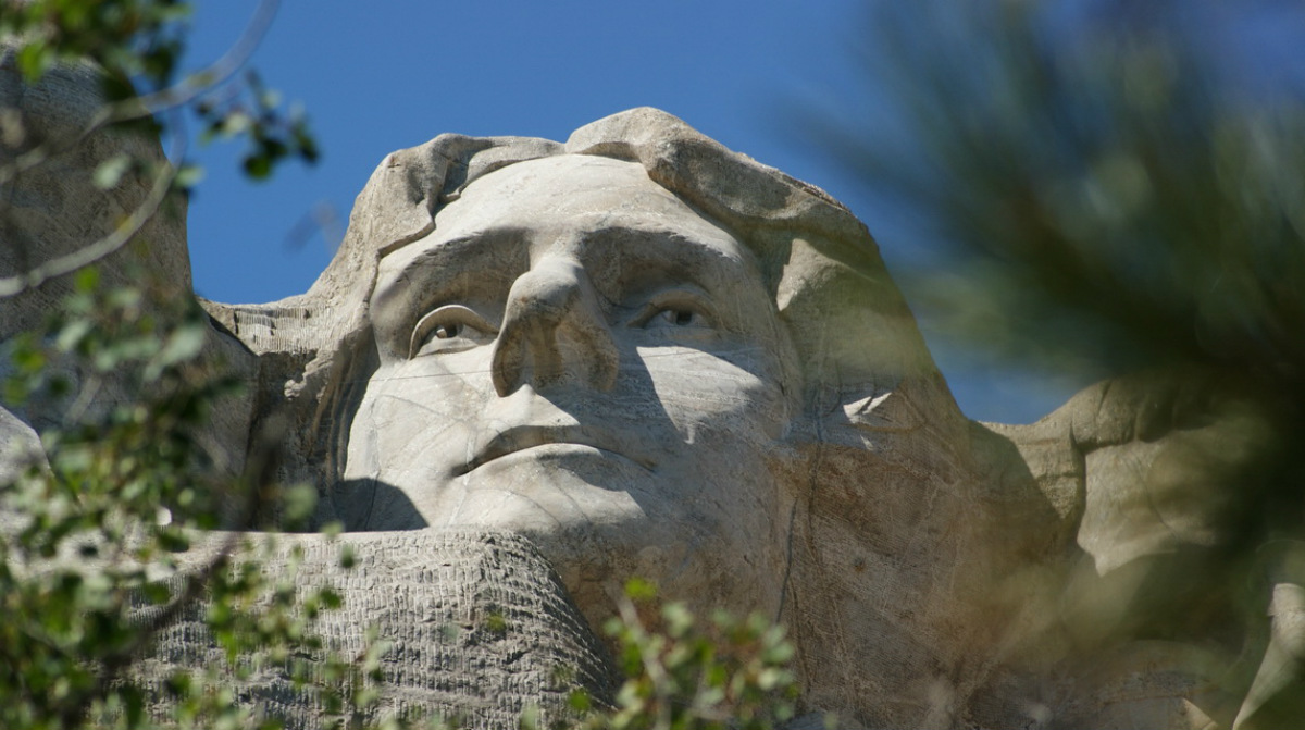 The stone face of Thomas Jefferson carved into the side of Mount Rushmore looks out.