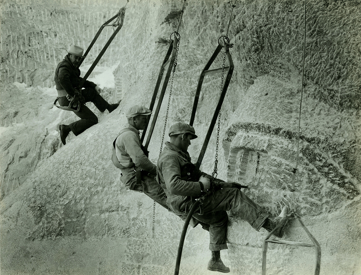 A historic photo of workmen hanging by ropes on the side of Mount Rushmore using tools to carve the eyes of a face into the stone.