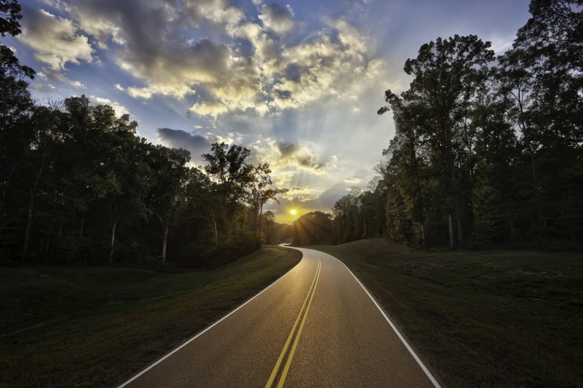 The Natchez Trace Parkway winding into the sunset with forest on each side of the road