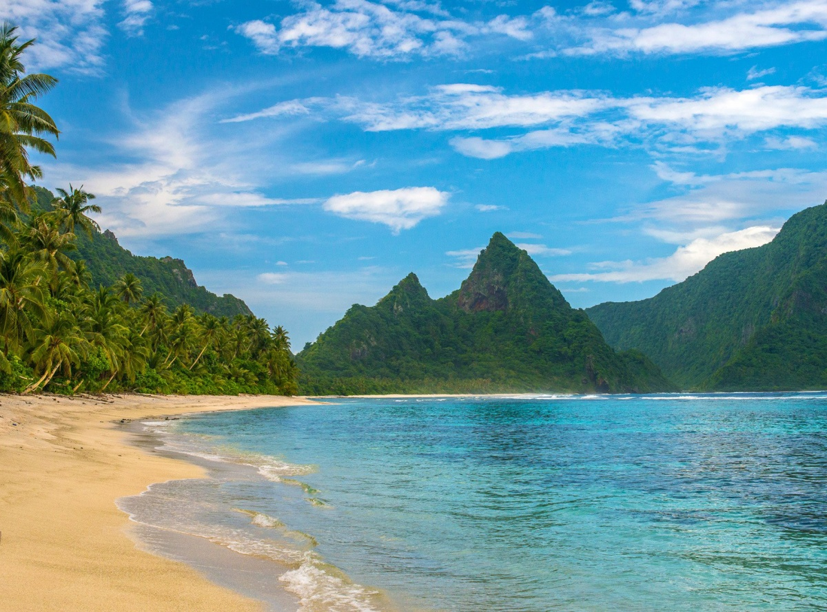 sandy beach, blue water, palm trees and green mountains
