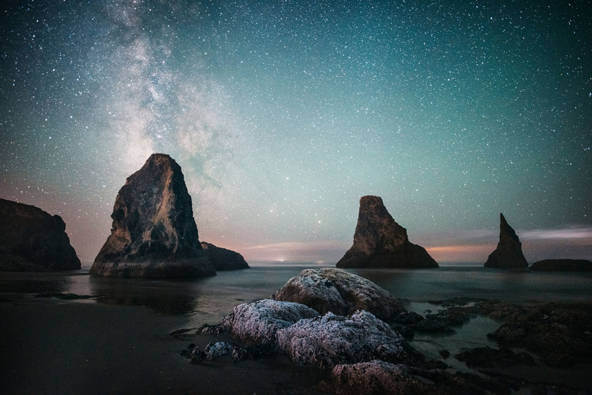 A bright aqua sky is filled with stars. It shines above a seashore where large rocks extend into the sky.