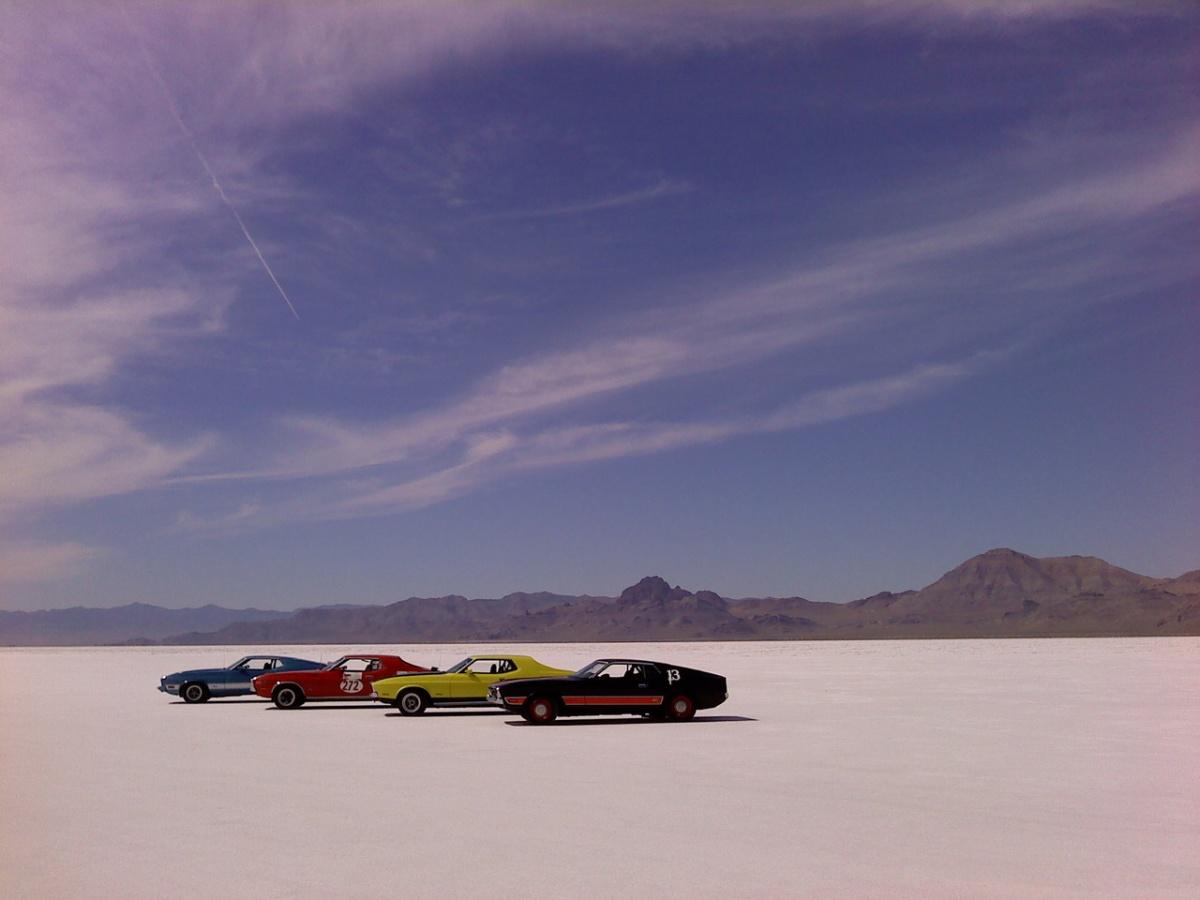 Four cars sit on the extremely flat Bonneville Salt flats while large mountains loom in the distance
