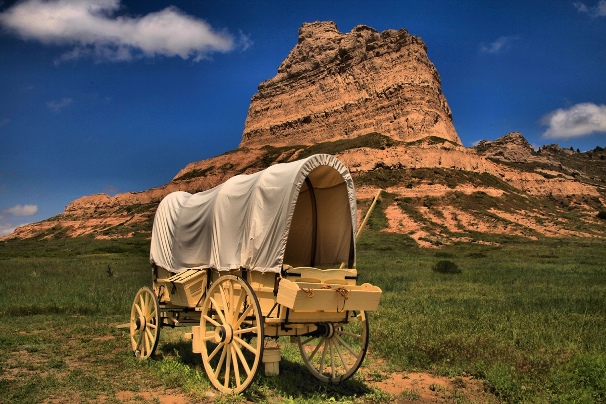 A covered wagon sits in front of land formation