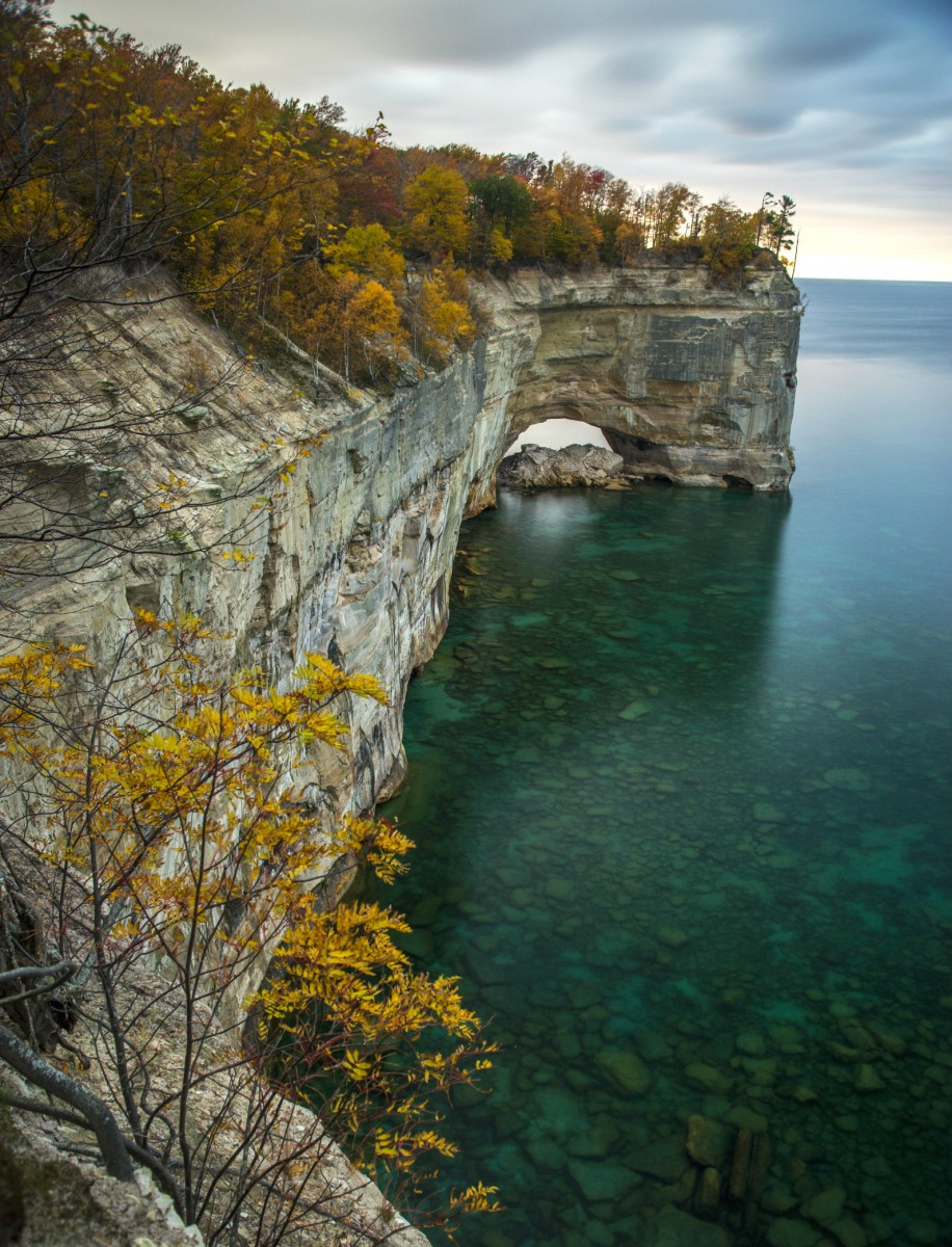 Trees grow on top of a stone cliff rising above the blue waters of a large lake.