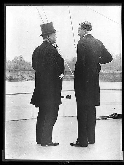 President Theodore Roosevelt and Gifford Pinchot stand talking in a black and white photo from 1907.