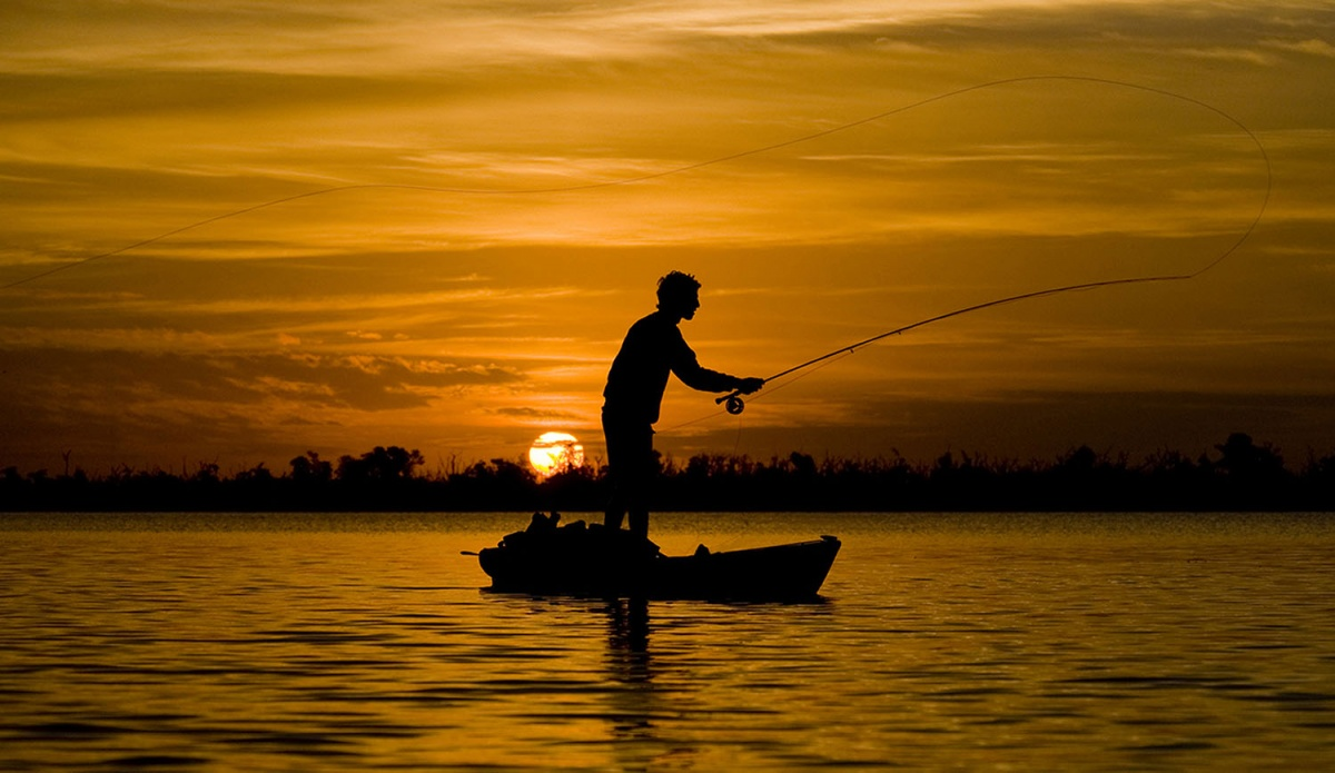 Man fishes off small boat in the middle of large body of water, the  sun sets in the background illuminating the sky in orange