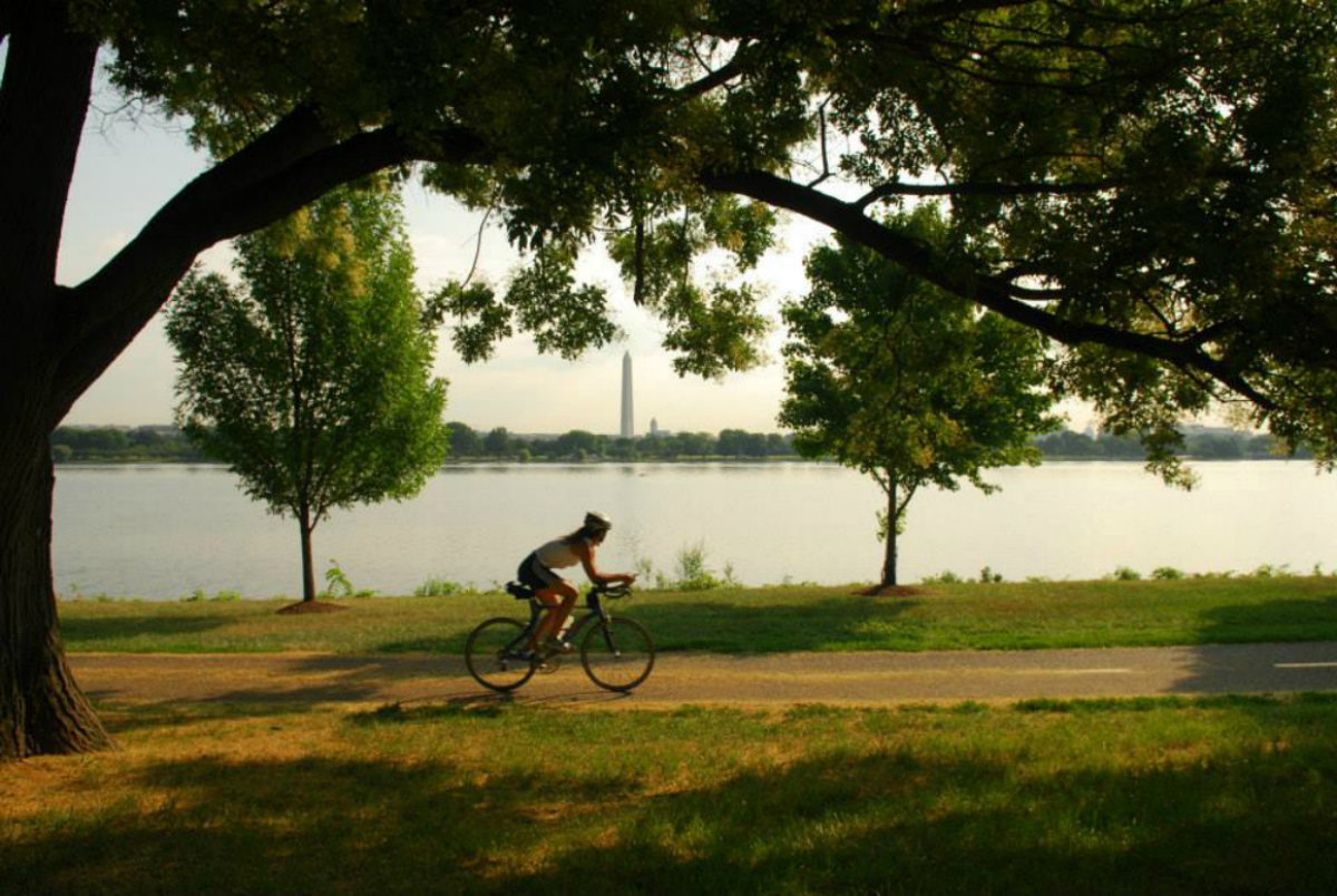 A biker rides along a paved path with a river and the Washington Monument in the background