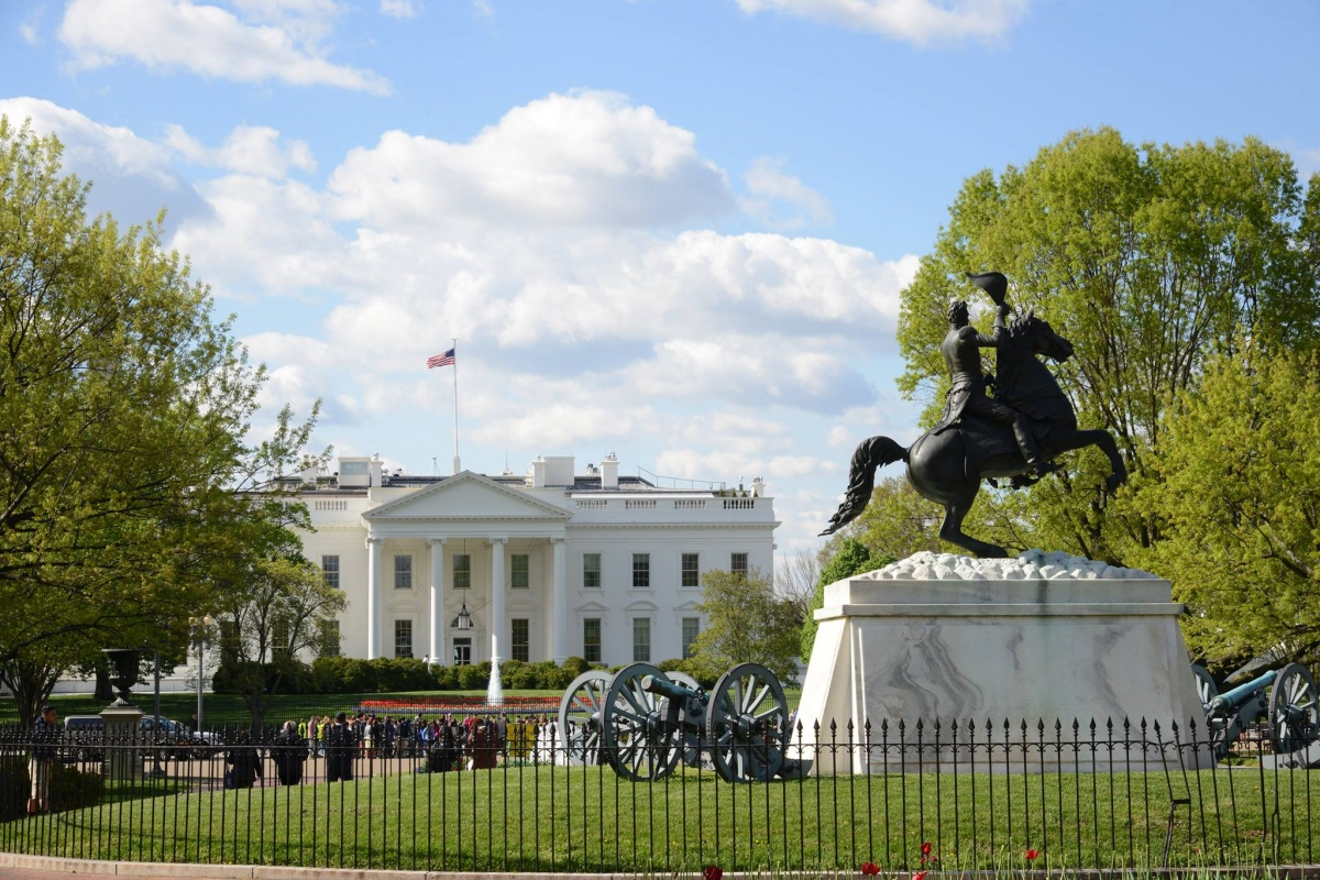 A statue of a man riding a horse stands in the middle of a bright green park in front of the fenced-in White House. An american flag is waving against the clouded blue sky.